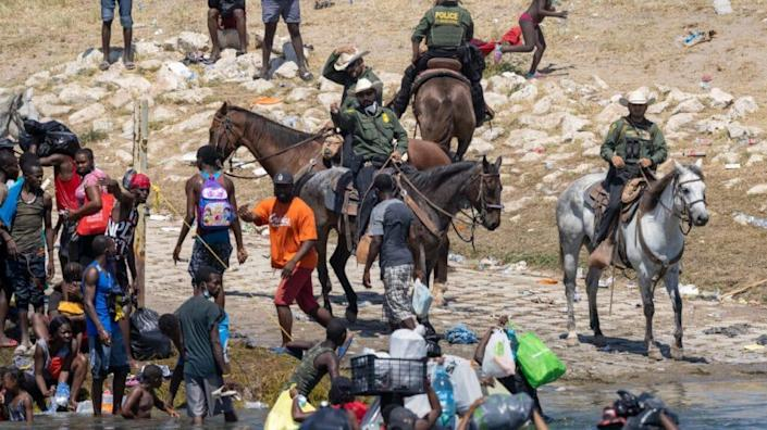 U.S. Border Patrol agents interact with Haitian immigrants on the bank of the Rio Grande in Del Rio, Texas on September 20, 2021 as seen from Ciudad Acuna, Mexico. (Photo by John Moore/Getty Images)