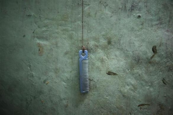 A comb tied with a rope is pictured inside a one room dwelling in a residential area in Mumbai October 5, 2011. Ten migrant workers who pay a monthly rent of 6,000 rupees ($123) live in a 4.5 x 3 meters (15 x 10 ft.) room. All the occupants who come from the same district of the northern Indian state of Uttar Pradesh are in Mumbai for better job opportunities and work as taxi drivers and manual laborers. According to a 2011 census conducted by the government of India, the population of Mumbai is more than 12 million and there is estimated to be about 20,482 persons per square kilometer.