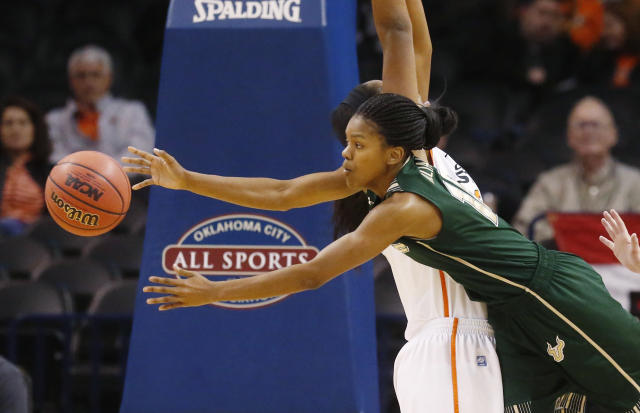 South Florida guard Courtney Williams (10) passes around Oklahoma State center LaShawn Jones (55) in the first half of an NCAA college basketball game at the All College Classic in Oklahoma City, Saturday, Dec. 14, 2013. (AP Photo/Sue Ogrocki)