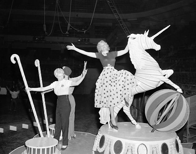 """<p>Getting ready for the unfolding of the symbolic """"big top"""" for the 1953 season, circus folk from Ringling Bros. and Barnum and Bailey Circus limber up at Madison Square Garden in New York, March 31, 1953, where the show makes its debut on April 1. Ann Mace, right, former Diamond Horseshoe showgirl, in street clothes, rides on the featured float, """"The Spirit of Candy Land,"""" from the """"Spectacle"""" number. (AP Photo/Ed Ford) </p>"""