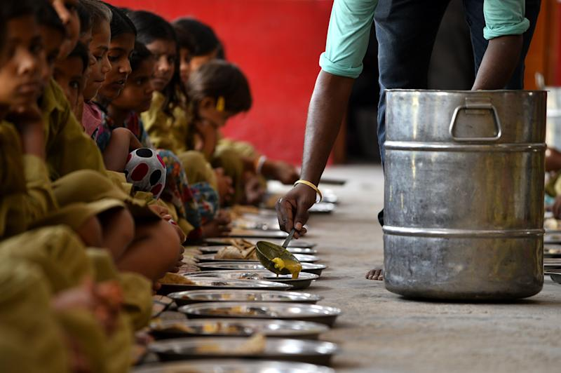 TO GO WITH India-education-school-health-food,FEATURE by Abhaya SRIVASTAVA In this photo taken on May 19, 2015, an Indian man serves lunch, organised by the non-profit Akshaya Patra Foundation, to schoolgirls at Chaumuha Primary School on the outskirts of Vrindavan. Churning out 1.2 tonnes of curry in under an hour, women stirring vats in the spotlessly clean, high-tech kitchen are hoping to erase the shocking reputation of India's free school lunch scheme. AFP PHOTO / Chandan KHANNA (Photo credit should read Chandan Khanna/AFP/Getty Images)