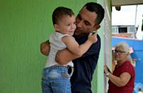 Colombian paralympian Juan Jose Florian plays with his son Juan Jose at home in the southeastern town of Granada, in November 2020