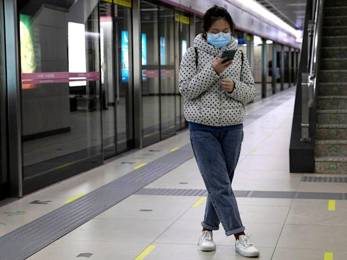 A woman waits for her train at a subway station after entering with a green pass in Wuhan on April 1, 2020.
