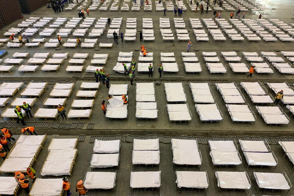Workers set up beds at an exhibition centre that was converted into a hospital in Wuhan in China's central Hubei province on February 4, 2020. - The Wuhan government said it plans to convert three existing venues, including a gymnasium and an exhibition centre, into hospitals to take in patients with mild symptoms of the new coronavirus that has so far claimed more than 400 lives. (Photo by STR / AFP) / China OUT (Photo by STR/AFP via Getty Images)