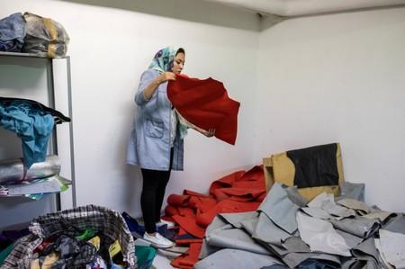 Afghan refugee and designer-maker Fariba Amini, 31, selects sheets from discarded refugee dinghies for her creations in a studio in Athens