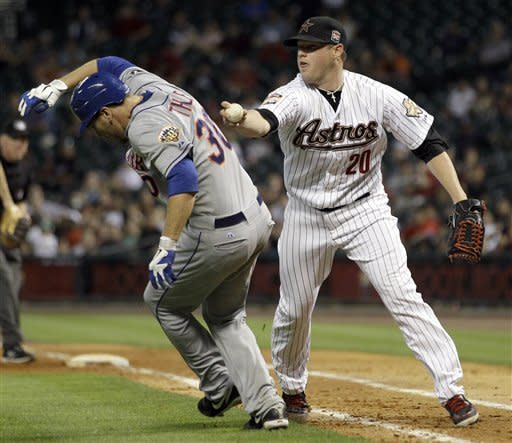 New York Mets' Josh Thole (30) is tagged out by Houston Astros starting pitcher Bud Norris (20) during the seventh inning of a baseball game Monday, April 30, 2012, in Houston. (AP Photo/David J. Phillip)