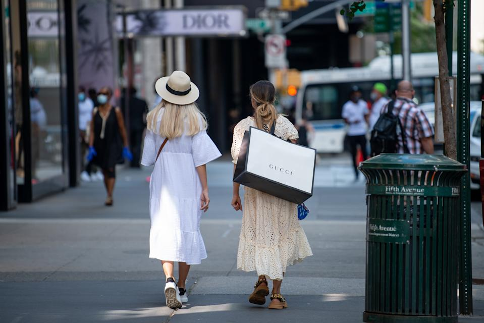 NEW YORK, NEW YORK - JUNE 24: A woman carries a mask and a Gucci shopping bag down a street as the city moves into Phase 2 of re-opening following restrictions imposed to curb the coronavirus pandemic on June 24, 2020 in New York City. Phase 2 permits the reopening of offices, in-store retail, outdoor dining, barbers and beauty parlors and numerous other businesses. New York state plans on re-opening in four phases. (Photo by Alexi Rosenfeld/Getty Images)