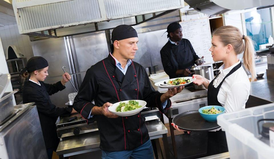 A chef handing a food order to a server in a restaurant kitchen.