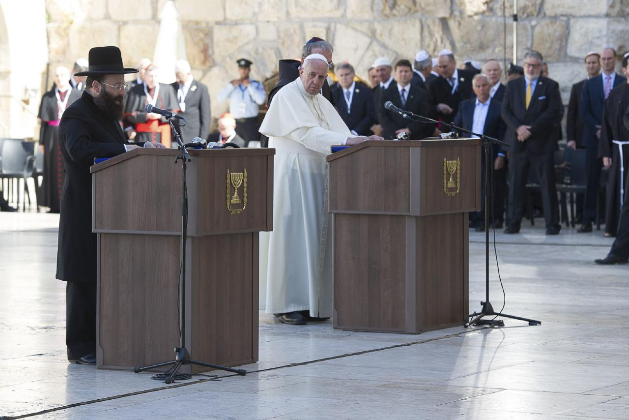 Pope Francis listens to Rabbi of the Western Wall Shmuel Rabinovitch (L) at the Western Wall, Judaism's holiest prayer site, in Jerusalem's Old City May 26, 2014. Pope Francis navigated the minefield of the Israeli-Palestinian conflict and humbly bowed to kiss the hands of Holocaust survivors on Monday, the last day of a Mideast trip laden with bold personal gestures. REUTERS/Osservatore Romano (JERUSALEM - Tags: RELIGION POLITICS) ATTENTION EDITORS - NO SALES. NO ARCHIVES. FOR EDITORIAL USE ONLY. NOT FOR SALE FOR MARKETING OR ADVERTISING CAMPAIGNS. THIS IMAGE HAS BEEN SUPPLIED BY A THIRD PARTY. IT IS DISTRIBUTED, EXACTLY AS RECEIVED BY REUTERS, AS A SERVICE TO CLIENTS