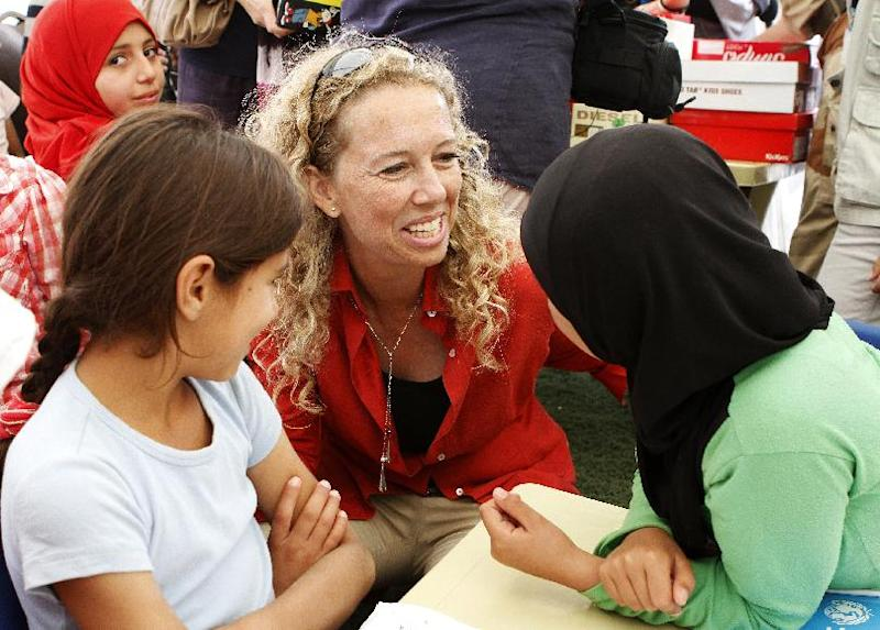 """In this Thursday, Oct. 4, 2012 photo, Dominique Hyde, UNICEF's representative to Jordan, speaks to Syrian refugee children during the opening of the first school at the Zaatari Syrian refugee camp in Mafraq, Jordan. For many Syrian children traumatized by the civil war and displacement from their homes, the opportunity to head back to school even if it's in a dusty, wind-swept refugee camp is a chance to return to a semblance of normalcy. Hyde, called Zaatari, """"the children's camp"""" as nearly half of Zaatari's 33,000 residents are under the age of 18.  She said it serves as an example of how the international community is trying to aid children bereft by the Syrian conflict. (AP Photo/ Raad Adayleh)"""
