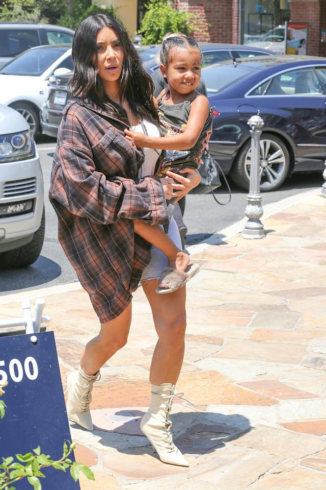 <p>In an over-sized flannel, white tank top, jean shorts and Yeezy heeled boots while heading to Color Me Mine in Calabasas, California. </p>