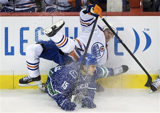 Edmonton Oilers' Eric Belanger, top, and Vancouver Canucks' Aaron Volpatti collide during the second period of an NHL hockey game in Vancouver, British Columbia, on Sunday, Jan. 20, 2013. (AP Photo/The Canadian Press, Darryl Dyck)