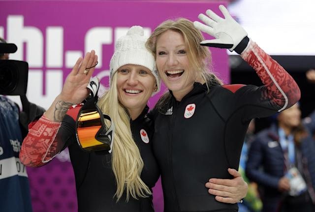 The team from Canada CAN-1, piloted Kaillie Humphries with brakeman Heather Moyse, wave to fans after their gold medal finish during the women's bobsled competition at the 2014 Winter Olympics, Wednesday, Feb. 19, 2014, in Krasnaya Polyana, Russia. (AP Photo/Jae C. Hong)