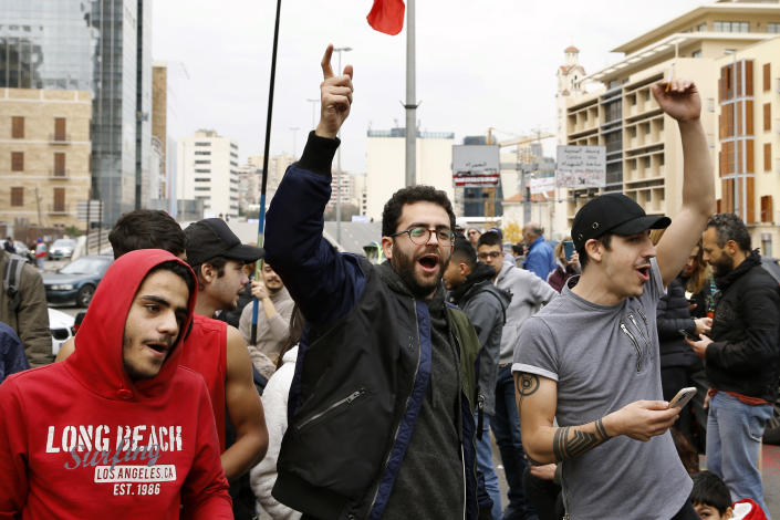 Anti-government protesters chant slogans as they block a main highway by garbage containers in Beirut, Lebanon, Friday, Jan. 17, 2020. Protesters closed major roads in the capital Beirut and around wide parts of Lebanon paralyzing the country as the political crisis over the formation of a new government worsens. (AP Photo/Bilal Hussein)