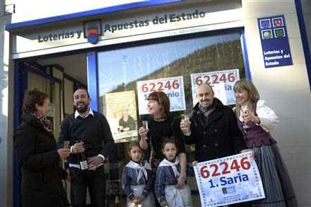 "The Garai family, owners of a lottery shop which sold part of the first prize of Spain's Christmas Lottery ""El Gordo"" (The Fat One) , amounting to 172 million euros, celebrate outside their shop in Mondragon, December 22, 2013. REUTERS/Andrea Comas REUTERS/Vincent West"