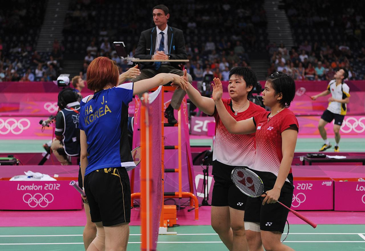 LONDON, ENGLAND - JULY 31: Greysia Polii and Meiliana Jauhari of Indonesia shake hands with Jung Eun Ha and Min Jung Kim of Korea in their Women's Doubles Badminton on Day 4 of the London 2012 Olympic Games at Wembley Arena on July 31, 2012 in London, England.  (Photo by Michael Regan/Getty Images)