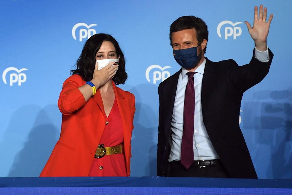 Madrid regional president and People's Party (PP) candidate Isabel Diaz Ayuso (L) blows a kiss beside PP leader Pablo Casado at the People's Party (PP) headquarters in Madrid as they celebrate their result after the Madrid regional elections on May 4, 2021. - Spain's right-wing People's Party led by rising star Isabel Diaz Ayuso won a resounding victory in Madrid's regional elections today handing a stinging defeat to Prime Minister Pedro Sanchez's Socialists, partial results showed. With more than 50 percent of the votes counted, Ayuso more than doubled her party's showing in the 2019 ballot, winning 63 of the parliament's 136 seats, while the Socialists shed 11 mandates to secure just 26. (Photo by PIERRE-PHILIPPE MARCOU / AFP) (Photo by PIERRE-PHILIPPE MARCOU/AFP via Getty Images)