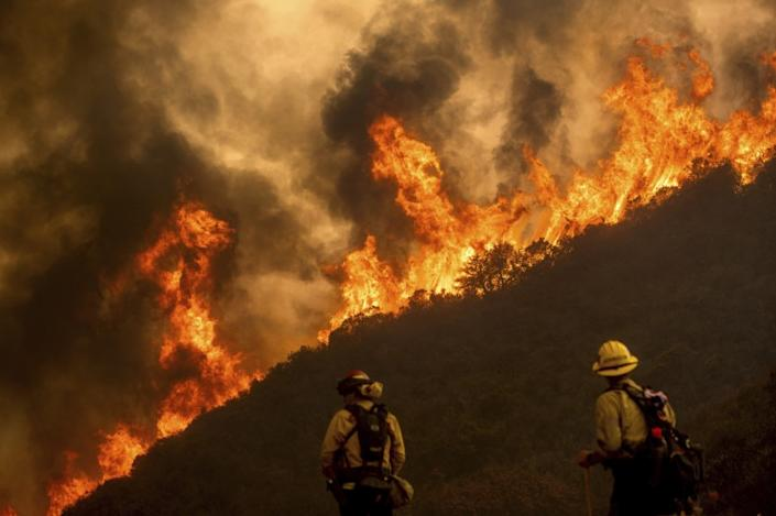 "Flames from the River fire crest a ridge as firefighters Ian Johnson, right, and Mike Campbell protect a home in Salinas, Calif., on Aug. 17. <span class=""copyright"">(Noah Berger / Associated Press)</span>"