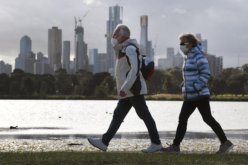 People walk along Albert Park lake in Melbourne on July 13, 2020, as five million people in Australia's second-biggest city began a new lockdown following a resurgence of coronavirus cases. (Photo by William WEST / AFP) (Photo by WILLIAM WEST/AFP via Getty Images)