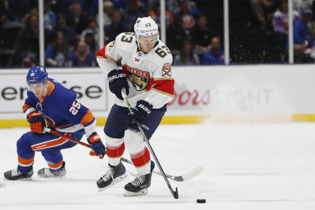 Florida Panthers right wing Evgenii Dadonov (63) corrals the puck in front of New York Islanders defenseman Devon Toews (25) during the first period of an NHL hockey game Saturday, Oct. 12, 2019, in Uniondale, N.Y. (AP Photo/Kathy Willens)