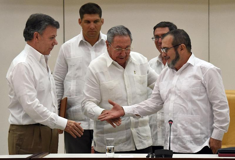 The head of the FARC guerrilla group Timoleon Jimenez, aka Timochenko (R), extends his hand to shake with Colombian President Juan Manuel Santos (L) in front of Cuban President Raul Castro (C) during a meeting in Havana on September 23, 2015 (AFP Photo/Luis Acosta)