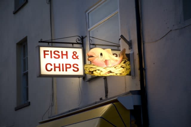 Fish and chip shop sign illuminated at night, Harwich, Essex