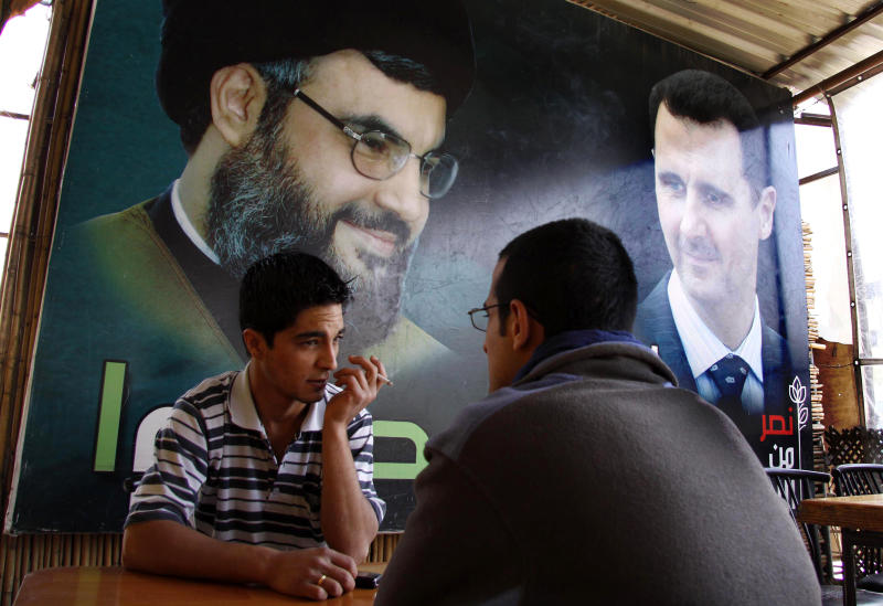 FILE - In this May 9, 2009 file photo, two Syrian men sit at a coffee shop under a big poster showing Syrian President Bashar Assad, right, and Hezbollah leader Sheik Hassan Nassrallah, left, in Damascus, Syria. U.S. officials said Israel launched a rare airstrike inside Syria on Wednesday. The target was a convoy believed to be carrying anti-aircraft weapons bound for Hezbollah, the powerful Lebanese militant group allied with Syria and Iran. The Israeli airstrike comes at a particularly sensitive and vulnerable time for Hezbollah in Lebanon. Despite its formidable weapons arsenal and political clout in the country, the group's credibility and maneuvering space has been significantly reduced in the past few years, largely because of the war in neighboring Syria but also because of unprecedented challenges at home. (AP Photo/Ola Rifai, File)