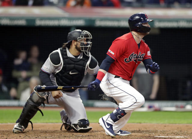 Cleveland Indians' Tyler Naquin watches his ball after hitting an RBI-single in the seventh inning of a baseball game against the Miami Marlins, Tuesday, April 23, 2019, in Cleveland. Carlos Gonzalez scored on the play. Miami Marlins catcher Jorge Alfaro watches. (AP Photo/Tony Dejak)