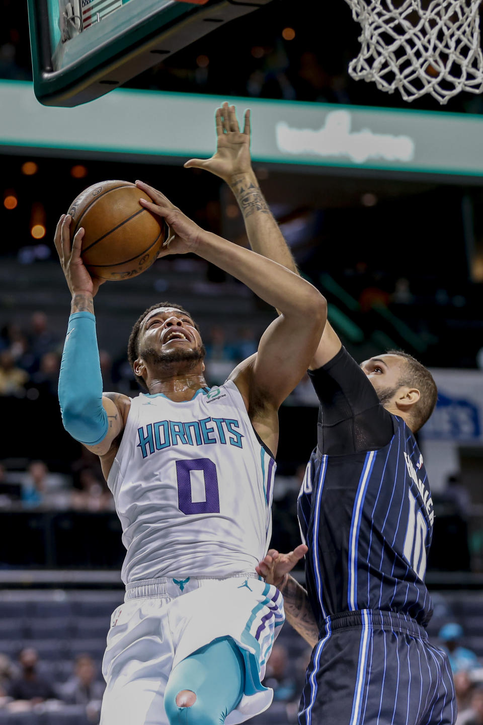 Charlotte Hornets forward Miles Bridges, left, shoots against Orlando Magic guard Evan Fournier in the first half of an NBA basketball game in Charlotte, N.C., Monday, Feb. 3, 2020. (AP Photo/Nell Redmond)