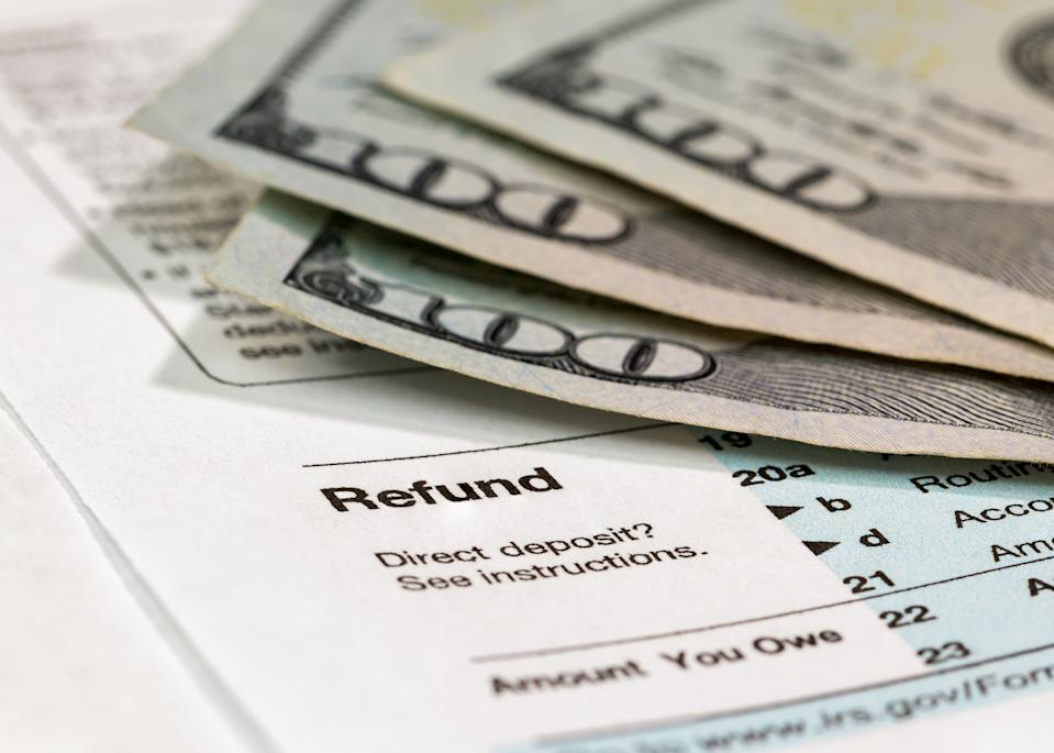 Income tax return form ready to be filled out with money in background