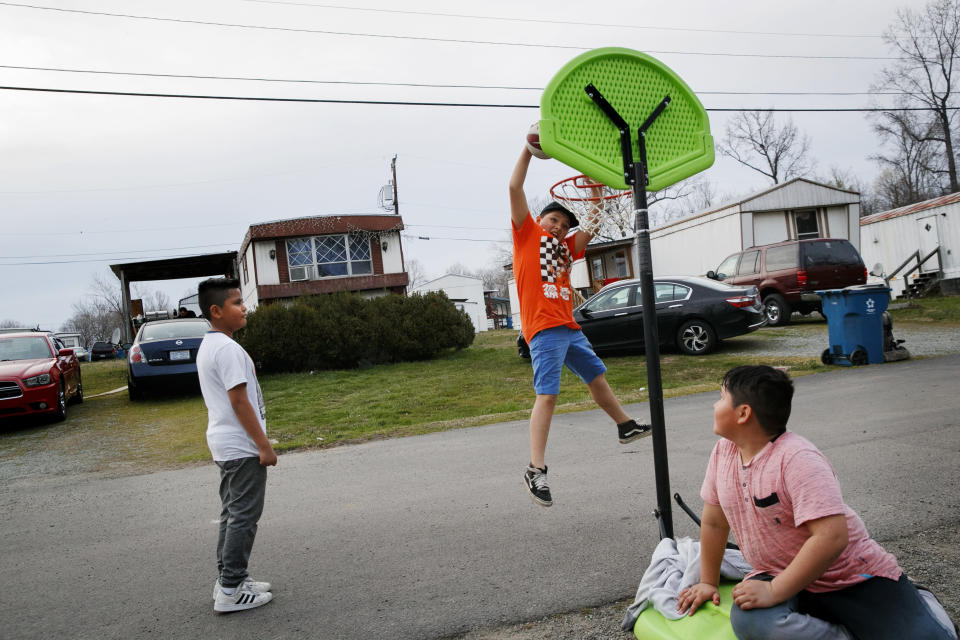 Sebastian Cervantes, 9, left, watches as Marvin Montoya, 10, makes a basket, next to Irvin Bahena, 10, in Burlington, N.C., Wednesday, March 11, 2020, at a largely Latino trailer community. (AP Photo/Jacquelyn Martin)