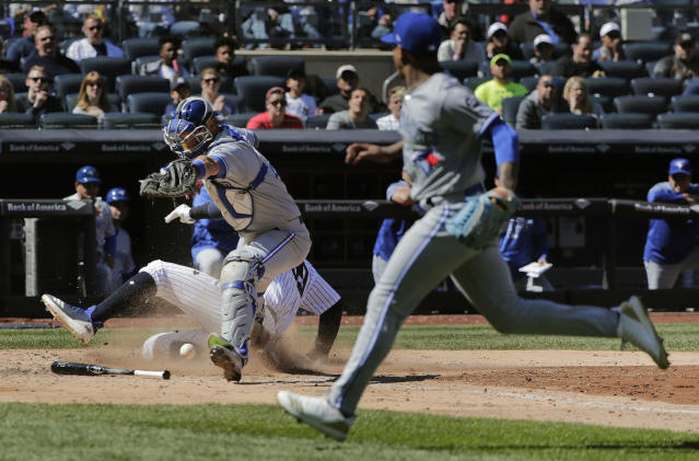 Toronto Blue Jays catcher Luke Maile drops the throw from pitcher Marcus Stroman, right, as New York Yankees' Aaron Judge slides safely into home plate on a bases-loaded infield grounder by Aaron Hicks during the sixth inning of a baseball game, Saturday, April 21, 2018, in New York. Judge was safe on the play. (AP Photo/Julie Jacobson)