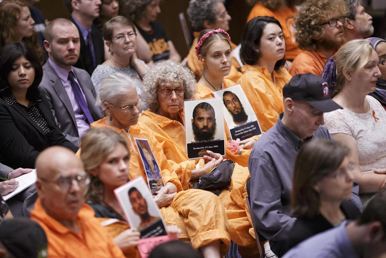 In a silent protest, audience members wearing orange jump suits, hold signs and photos of Guantanamo detainees during a hearing on Capitol Hill in Washington, Wednesday, July 24, 2013, by the Senate Judiciary subcommittee on Constitution, Civil Rights & Human Rights examining the fate of prisoners being indefinitely held in the war on terrorism. (AP Photo/J. Scott Applewhite)
