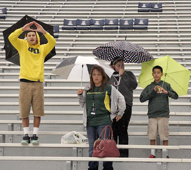 Oregon fans that are from New Mexico wait in the rain in an empty stadium for the game to start against Arizona in an NCAA college football game on Saturday, Nov. 23, 2013 in Tucson, Ariz. (AP Photo/John MIller)