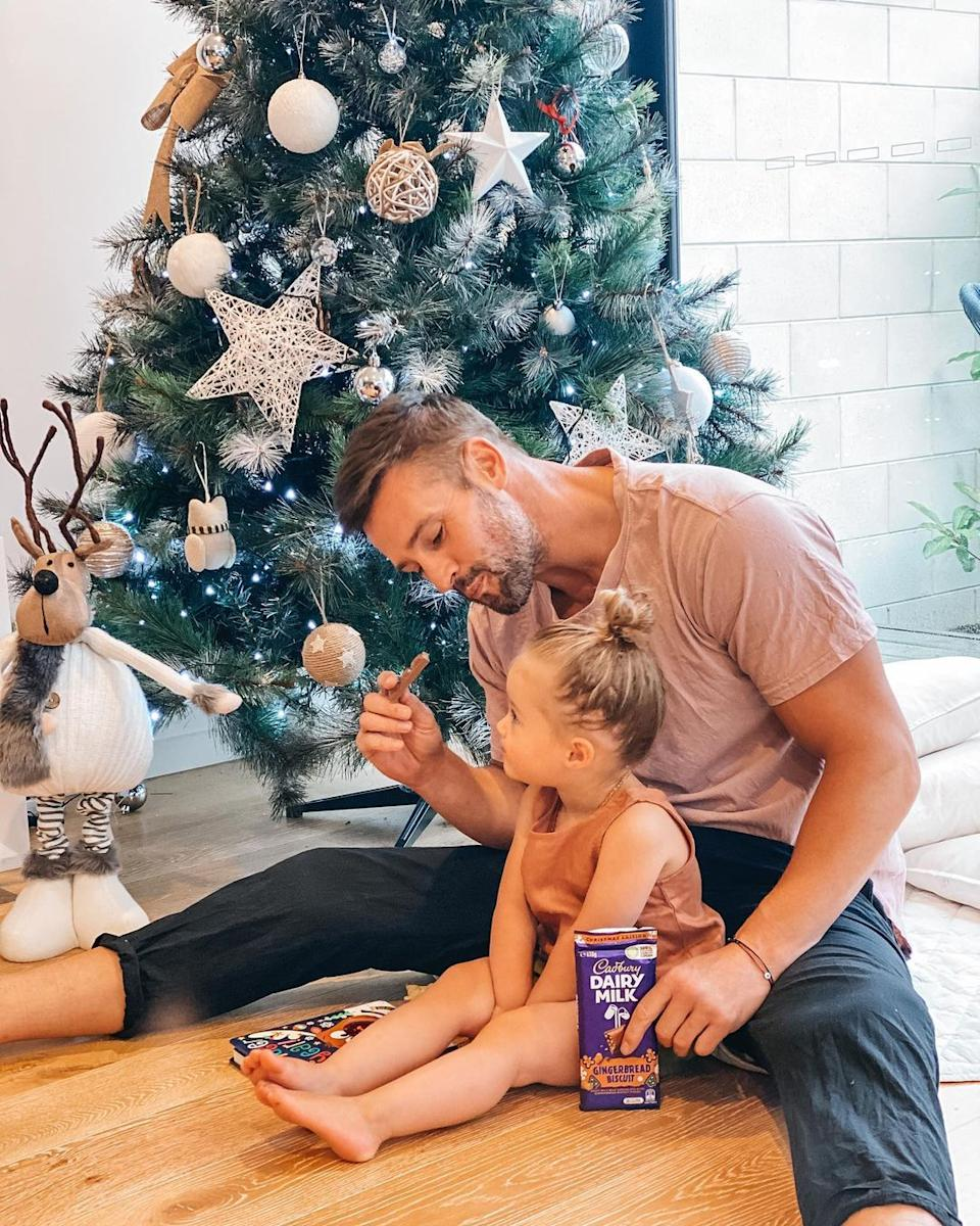 Kris Smith enjoyed a sweet treat in front of the tree with his almost-two-year-old daughter Mila. Photo: Instagram/krissmith13.