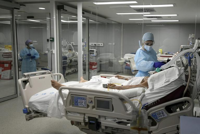 Healthcare workers attend to a patient at the Covid-19 Intermediate Care Unit (IMCU) of the Enfermera Isabel Zendal new emergency hospital, in Madrid, on January 27, 2021