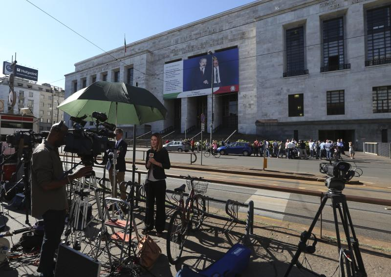 TV crews and media work outside Milan's court, Italy, Monday, June 24, 2013. Former Premier Silvio Berlusconi faces a verdict in his sensational sex-for-hire trial, charges that could bring an end to his two-decade political career. Berlusconi is charged with paying an under-age Moroccan teen for sex and then trying to cover it up with phone calls to Milan police officials when she was picked up for alleged theft. Berlusconi and the woman deny having had sex with each other. A court is expected to deliver a verdict Monday. (AP Photo/Luca Bruno)