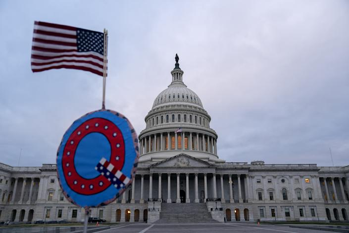 "A demonstrator holds a ""Q"" sign outside the U.S. Capitol in Washington on Wednesday, Jan. 6, 2021. (Stefani Reynolds/Bloomberg via Getty Images)"