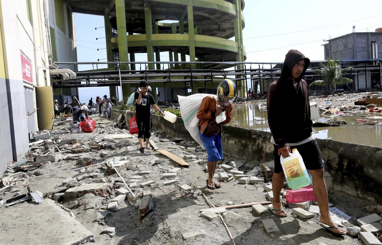 <p>In this Sunday, Sept. 30, 2018, file photo, people carry away items from a shopping mall badly damaged by a massive earthquake and tsunami in Palu, Central Sulawesi, Indonesia. (AP Photo/Tatan Syuflana, File) </p>