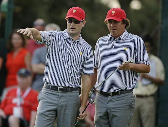 United States's Zach Johnson, left, discusses a putt with teammate Jason Dufner on the 10th green during a foursomes match at the Presidents Cup golf tournament at Muirfield Village Golf Club Friday, Oct. 4, 2013, in Dublin, Ohio. (AP Photo/Darron Cummings)