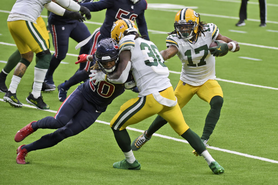Green Bay Packers wide receiver Davante Adams (17) runs with the ball as Packers running back Jamaal Williams (30) blocks Houston Texans safety Justin Reid (20) during the first half of an NFL football game Sunday, Oct. 25, 2020, in Houston. (AP Photo/Eric Christian Smith)