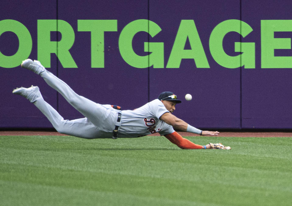 Detroit Tigers center fielder Victor Reyes can't catch a fly ball hit by Cleveland Indians' Cesar Hernandez during the first inning of a baseball game in Cleveland, Saturday, April 10, 2021. (AP Photo/Phil Long)