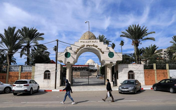 Palestinians walk past the entrance of the Legislative Council building in Gaza City, on 17 January, 2021. The UN has called on Israel to swiftly provide vaccines to Palestinians living in occupied territories. (AFP via Getty Images)