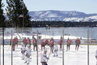 Members of the Colorado Avalanche, in white, and the Vegas Golden Knights, red, prepare to face off to start the first period of the Outdoor Lake Tahoe NHL hockey game in Stateline, Nev., Saturday, Feb. 20, 2021. (AP Photo/Rich Pedroncelli)
