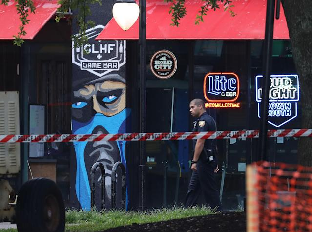 A Jacksonville Sheriff officer walks past the GLHF Game Bar where gamers Taylor Robertson and Elijah Clayton were killed on Sunday. (Getty Images)