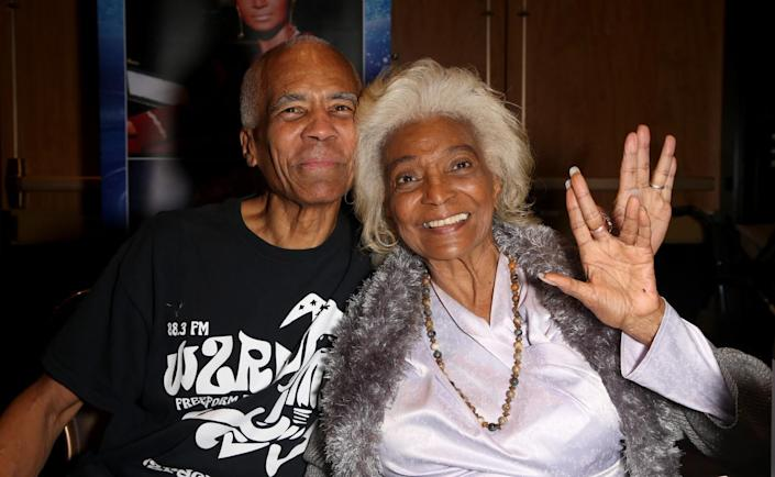 """A middle-aged man, left, smiling with his older mother, who is spreading her hand in a """"Star Trek"""" symbol."""