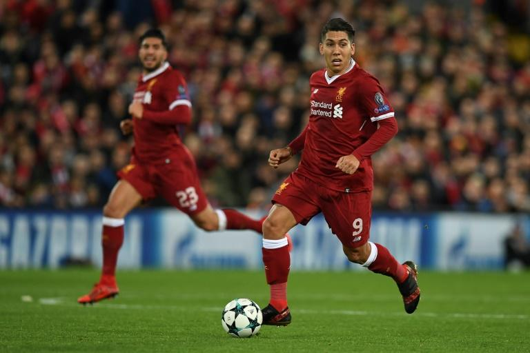 Liverpool's Roberto Firmino (R) runs with the ball during their match against Spartak Moscow in Liverpool, north-west England on December 6, 2017