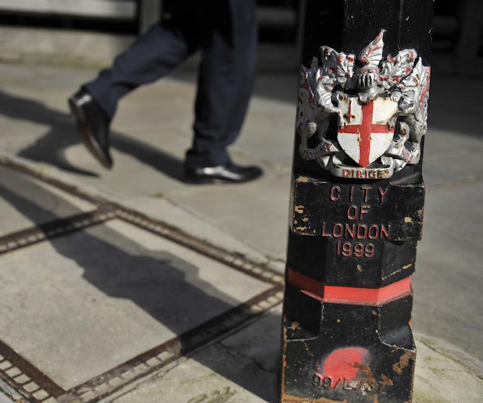 A worker walks past a bollard bearing the coat of arms of the City of London Corporation in London's Square Mile.