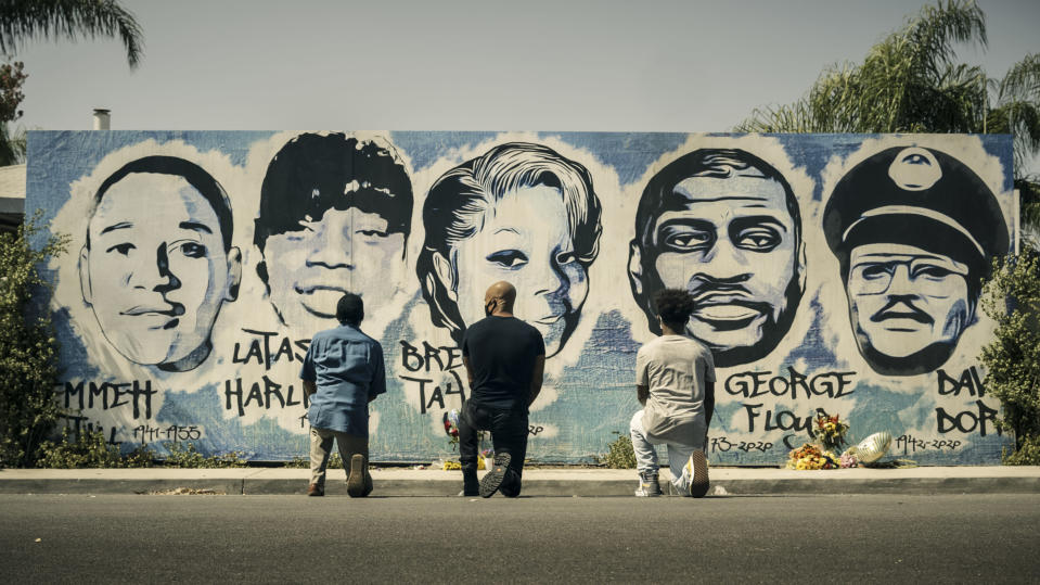 """This image released by CBS shows Obba Babatund, portraying Daniel Harrison Sr., from left, Shemar Moore, portraying his son Hondo, and Deshae Frost, as Darryl, kneel in front of a mural in a scene from """"S.W.A.T."""" In the episode titled, """"3 Seventeen Year Olds,"""" airing in the first hour of a two-hour season premiere episode on Nov. 11, the trio confront the history of racial tension in Los Angeles through flashbacks to the city in 1992 following the Rodney King verdict. (CBS via AP)"""