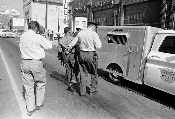 <p>A police officer holds the Rev. Martin Luther King Jr. by his belt as he leads him to the paddy wagon, following arrest at an anti-segregation protest in downtown Birmingham, Ala., on April 13, 1963. An unidentified cameraman is documenting the scene. (AP Photo) </p>